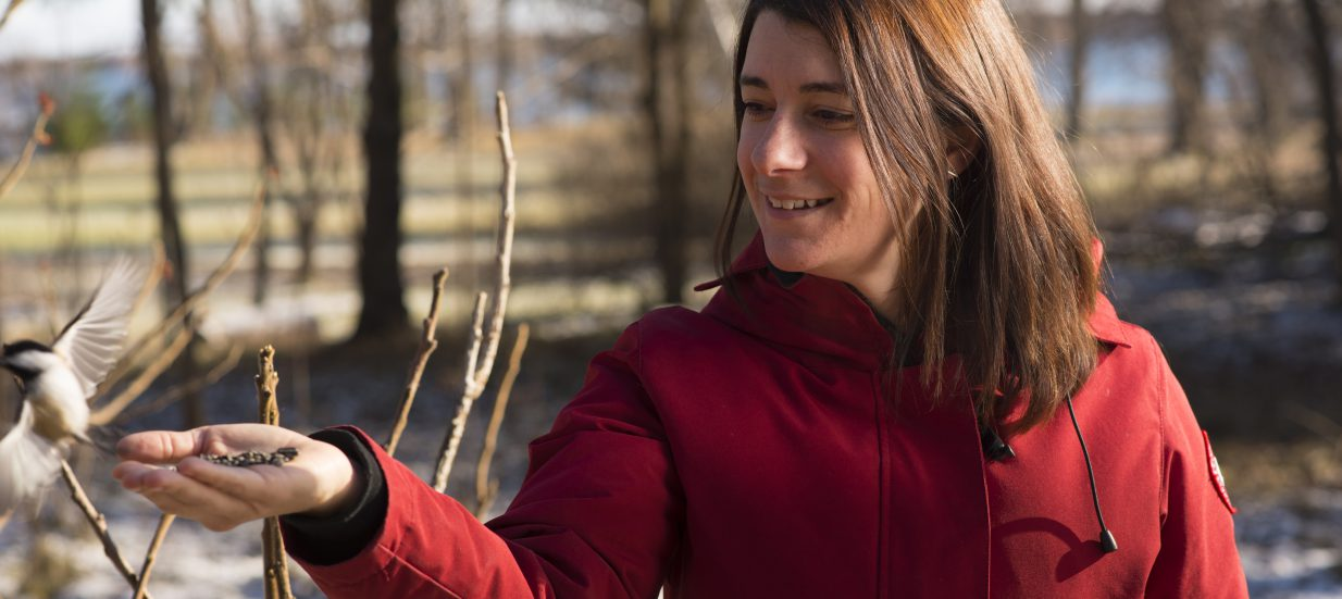 Jessica Spooner of Blue Bark & Co holding a bird on a nature hike.