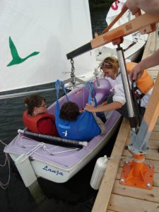 A lift transferring a person into the boat at Quinte SailAbility.
