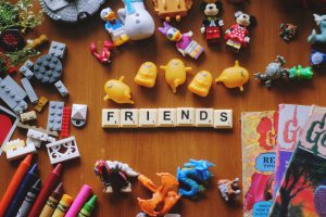"""Toys on a table and scrabble pieces that read """"friends"""""""