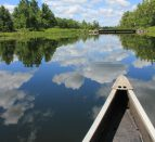 Edge of a canoe on the water of the Trent River.