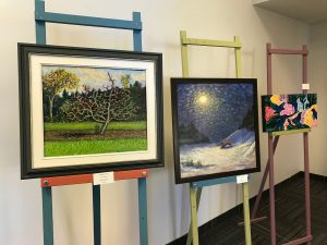 Three paintings lined up on easels at the Belleville Art Association Gallery.