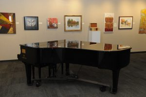 A large piano near a wall of paintings at the Parrott Gallery.