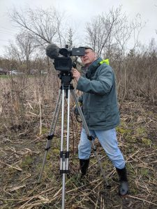 A man looks into a video camera on a tripod, standing outside.