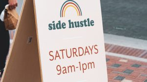 A white sandwich board with text: Side Hustle, Saturdays 9am-1pm.