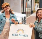 Kylie Aucoin and Heather Case stand on either side of a sandwich board sign for the Side Hustle Market.