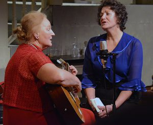 Two women playing guitar and singing on a stage.