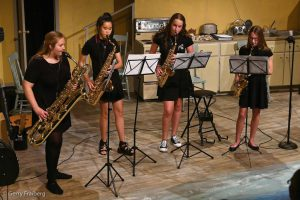 Four musicians playing saxophones at a Night Kitchen Too performance.
