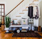 A collection of clothes, housewares and other thrifted items in front of a staircase.