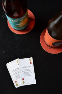 Two bottles of beer and business cards from Wild Card Brewing Co.