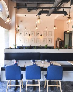 A modern restaurant dining room with blue chairs and industrial hanging lights.