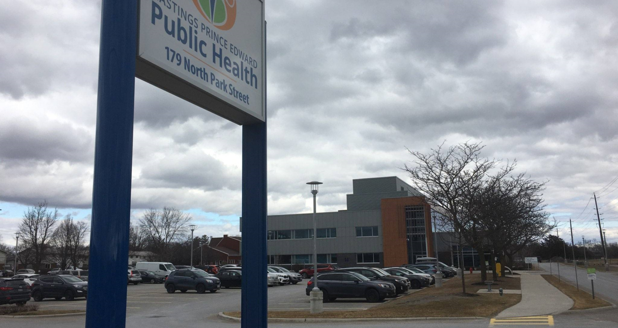 A sign for Hastings-Prince Edward Public Health in front of a parking lot.