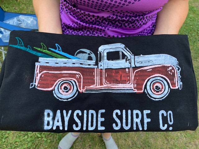 "A person holding a piece of wood painted with a red truck and text ""Bayside Surf Co"""