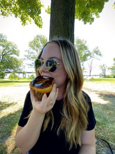 A person sitting in front of a tree eating a doughnut.
