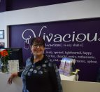 "A woman standing in front of a purple wall with a sign that says, ""Vivacious""."