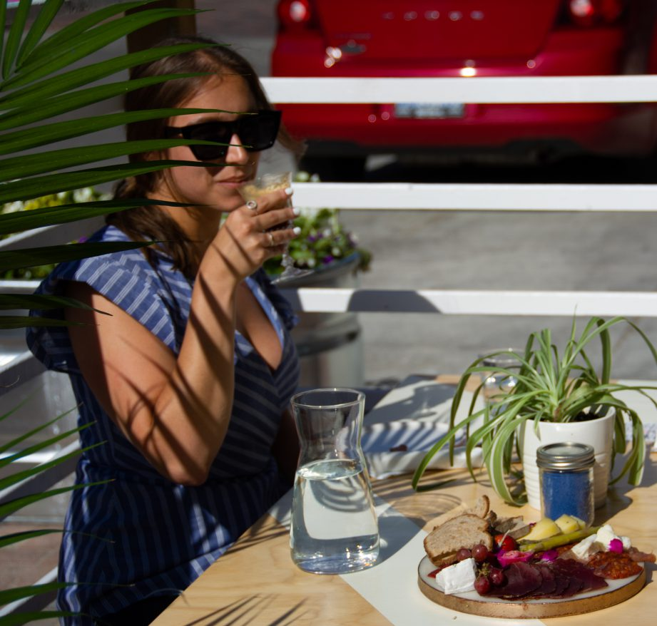 A person sitting on a patio holding a drink with a plate of food on the table.