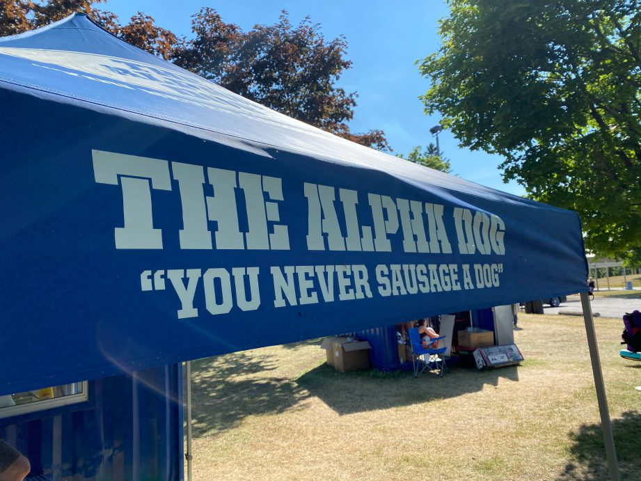 """A blue tent with text, """"The Alpha Dog""""."""