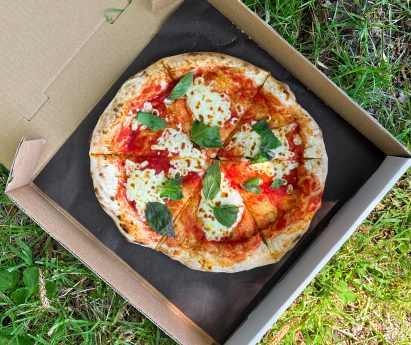 A box of pizza on the grass.