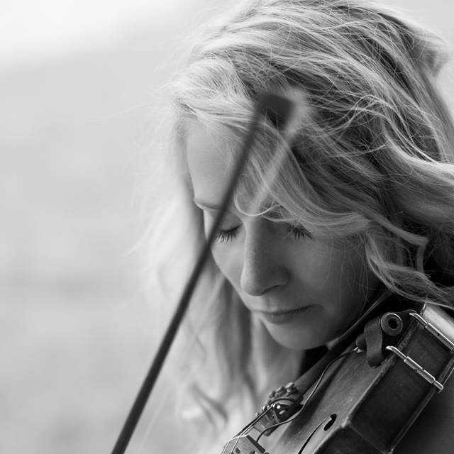 A black-and-white photo of a person playing a violin.