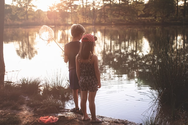 Two kids standing next to a pond.