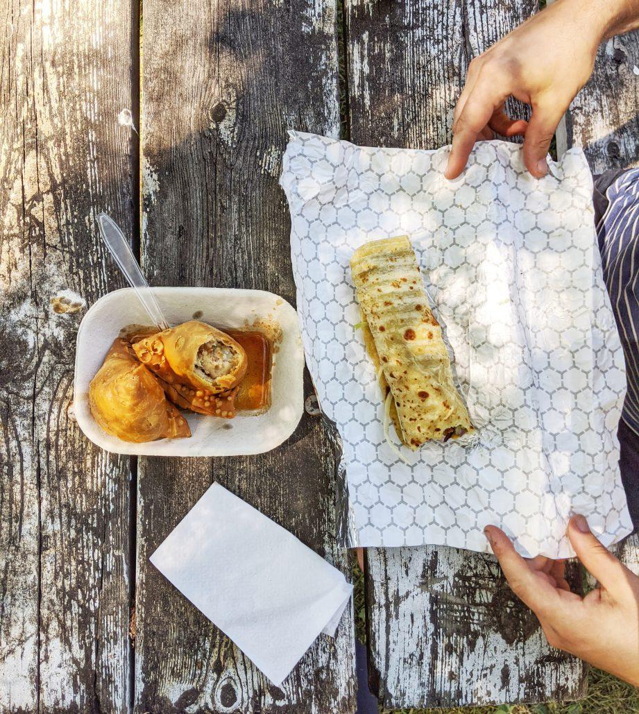 Samosas and a wrap on a picnic table.