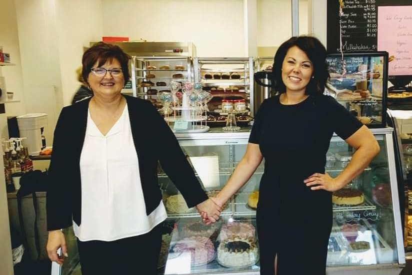 Two people standing in a bakery holding hands.