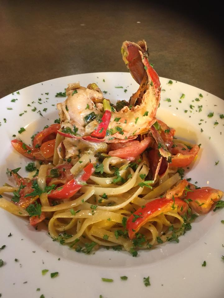 A white plate with pasta and shrimp.