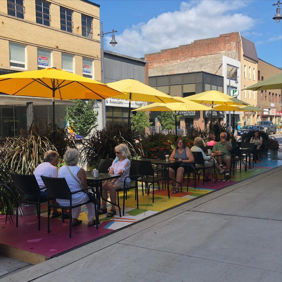 People sitting on a patio under yellow umbrellas. It's Al Fresco season in downtown Belleville, so make sure to try some of the patios this fall!