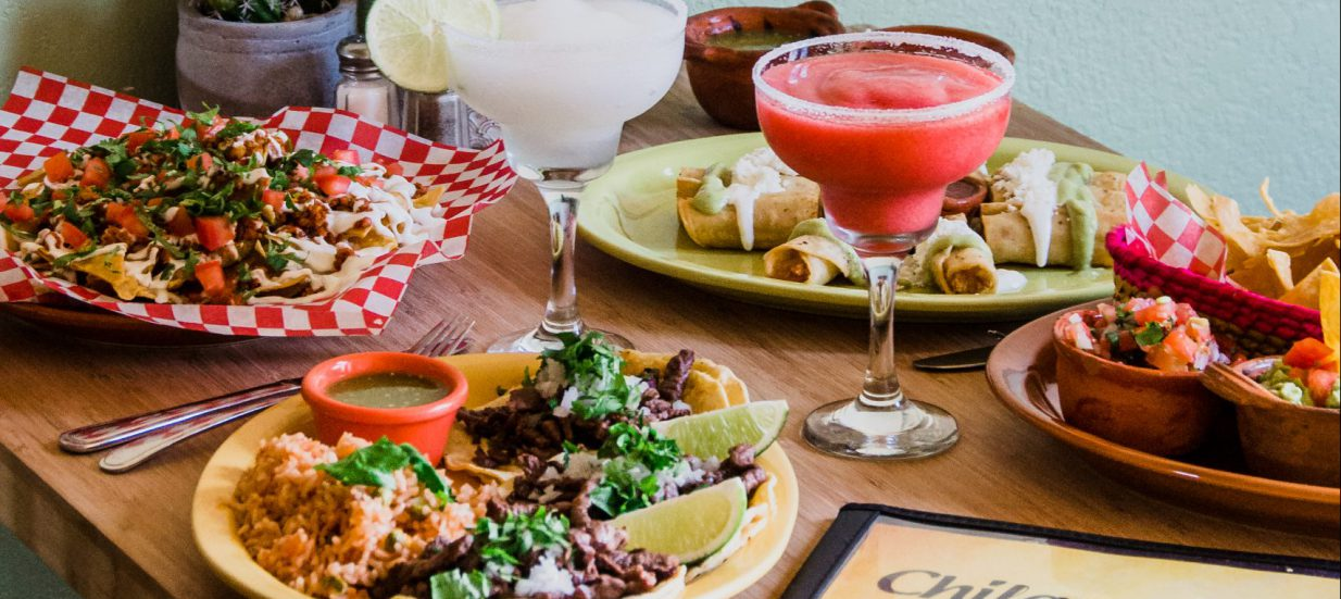 Plates of food and blended margaritas on a table with a menu at Chilangos Mexican Restaurant.