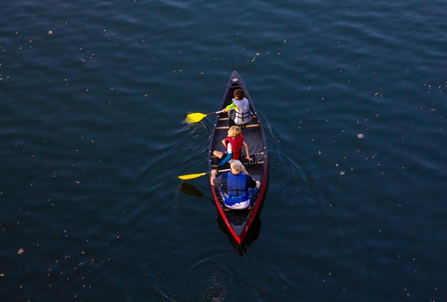 An aerial shot of three people in a canoe. Heading out for a ride on a canoe or kayak is a great family activity with kids this fall in Bay of Quinte.