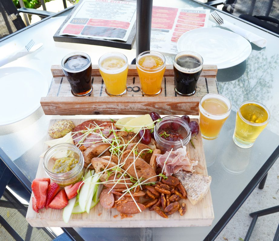 A flight of beers and charcuterie board on a patio table at Signal Brewing Co in Belleville.