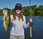 A person standing in front of a lake holding a fishing rod and a fish. Angler Ashley Rae is sharing 10 tips for new anglers.