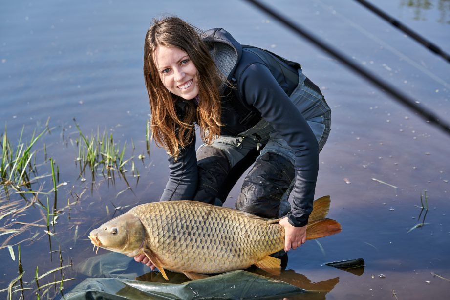 A person standing in the water holding a carp.
