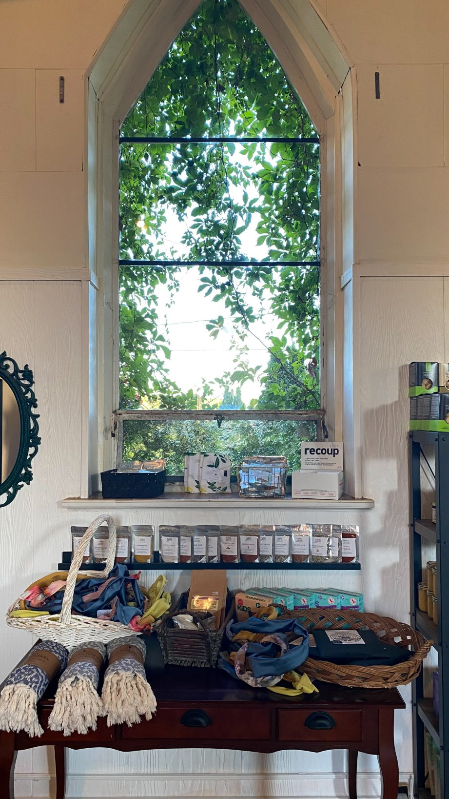 A window with a table in front of it holding various items.