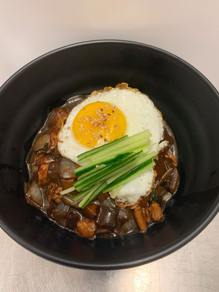 A black bowl filled with meat and vegetables, topped with a fried egg. Spice up your fall takeout routine with flavours from around the world, right here in Quinte West.