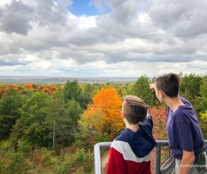 Two people pointing at colourful fall trees. Check out this family-friendly list of fall hikes in the Bay of Quinte by Kathryn Dickson of Kathryn Anywhere.