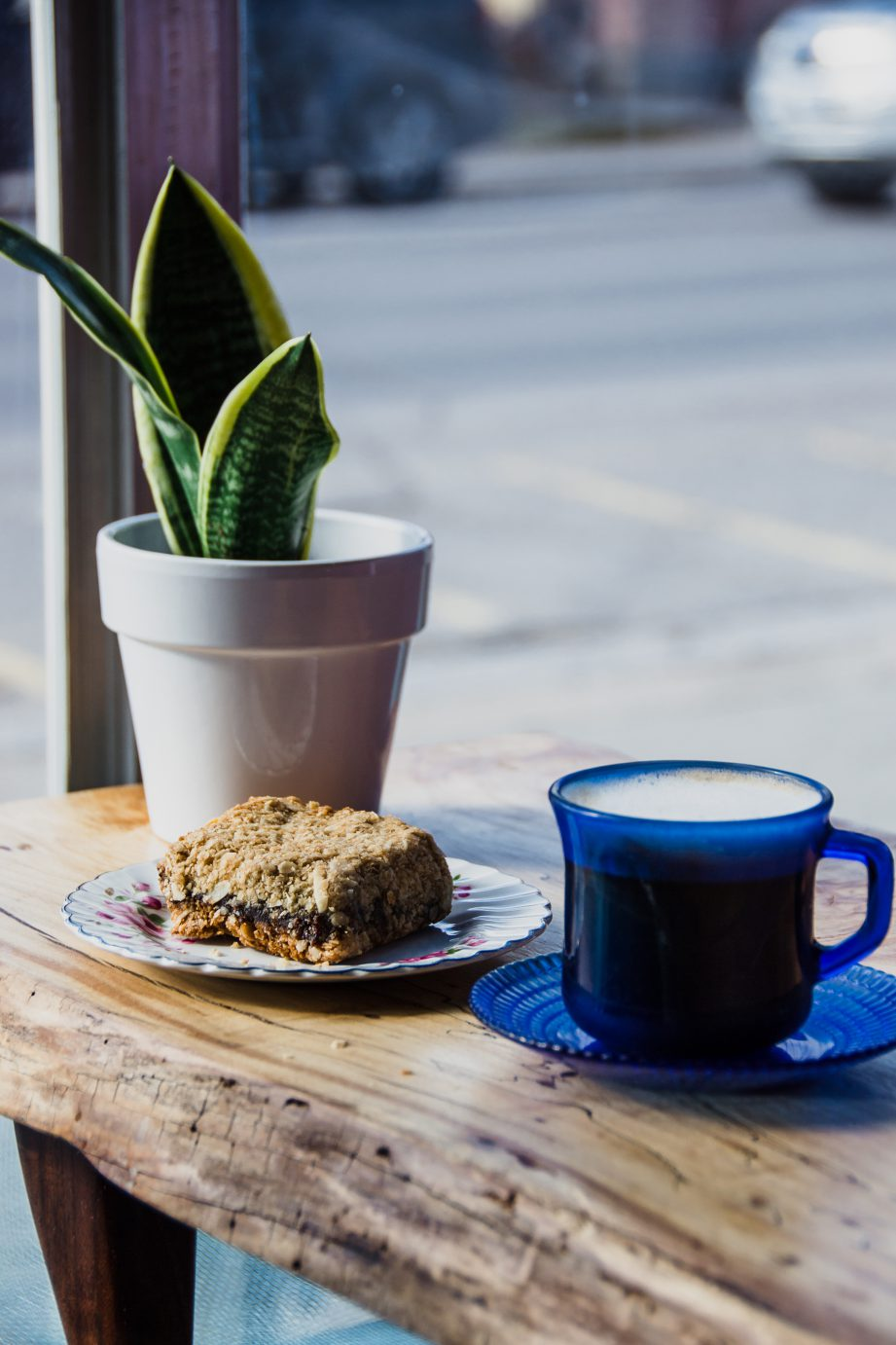 A coffee cup and a small plate with dessert on a wooden table.