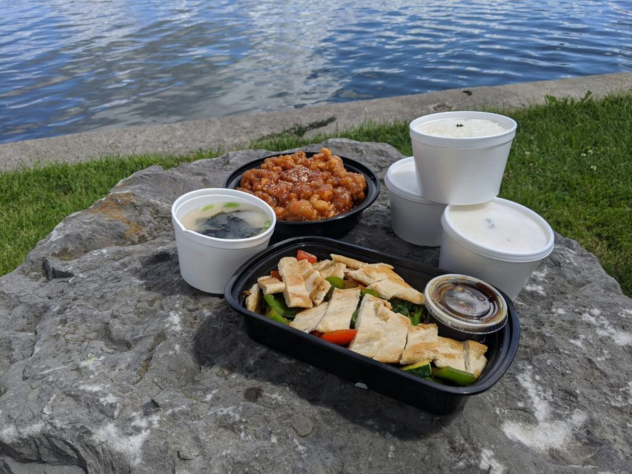 Takeout containers with food on a rock. Spice up your fall takeout routine with flavours from around the world, right here in Quinte West.