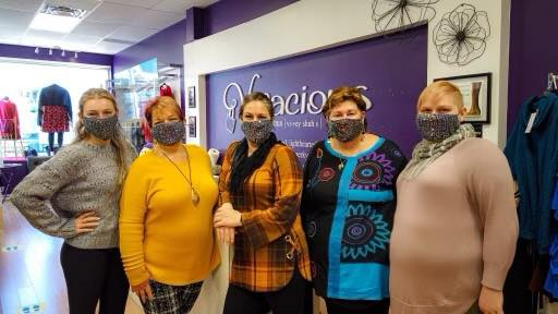 """Five people wearing masks standing in front of a purple wall with text: """"Vivacious"""""""