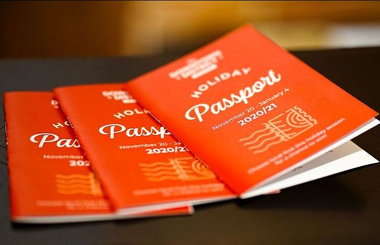 Three red booklets with white text: Holiday Passport 2020/21