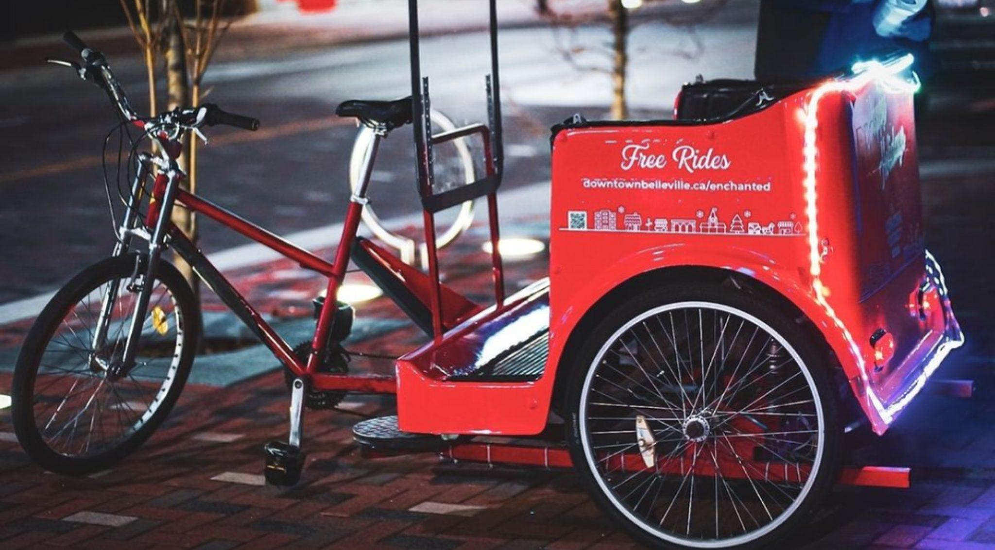 A red pedicab on a sidewalk at night.