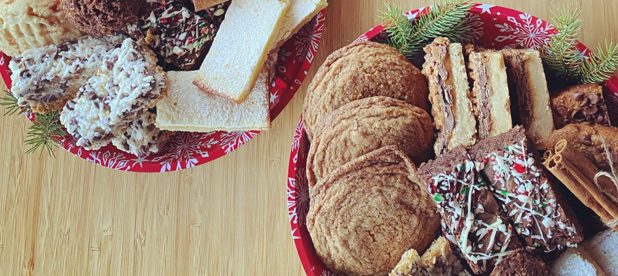 Plates of assorted Christmas cookies on a wood table.
