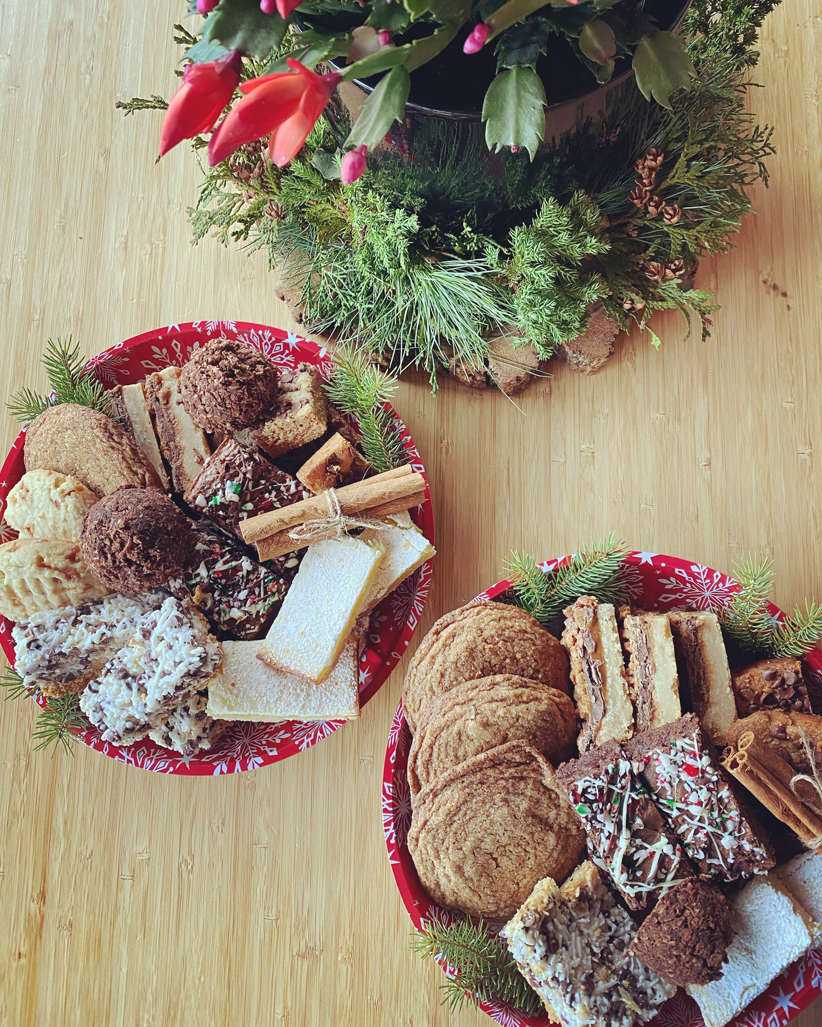 Plates of assorted holiday cookies on a wood table.
