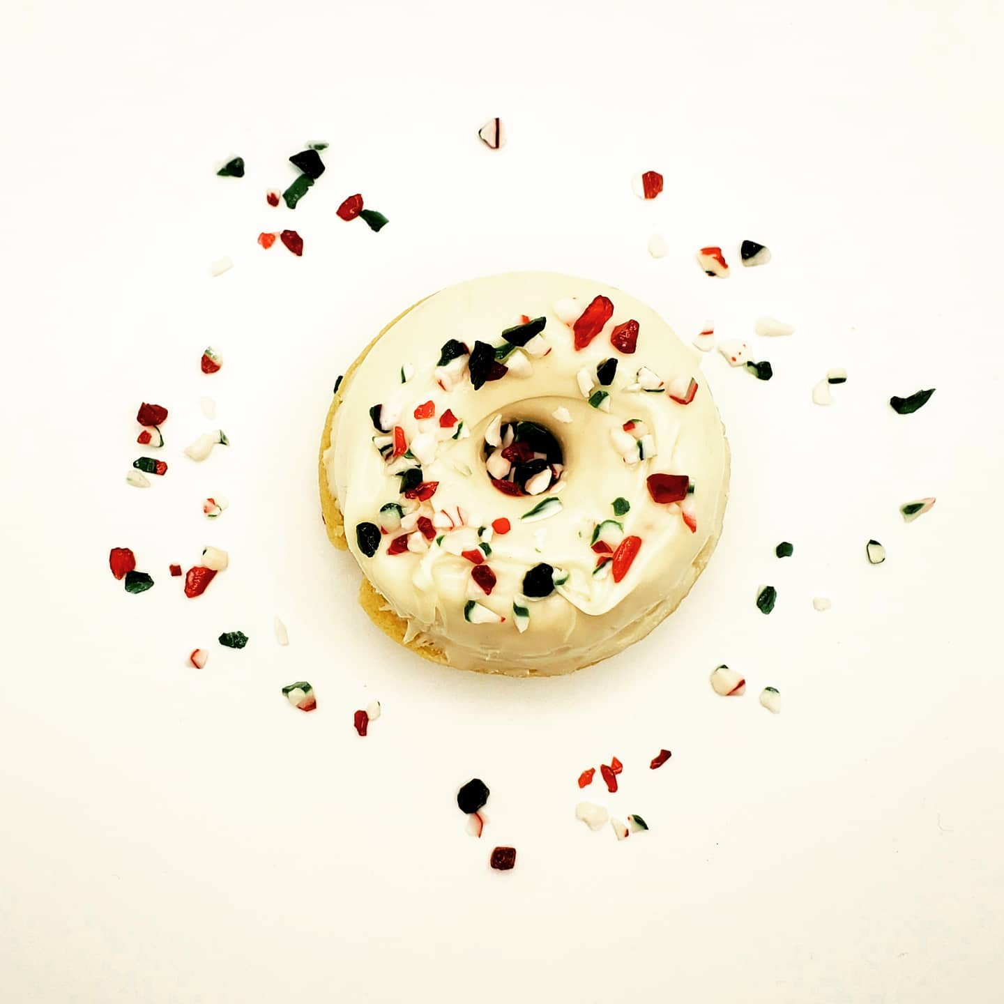 A doughnut with white icing and crushed candy canes on a white background.