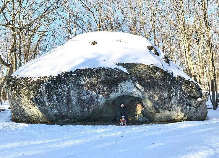 A person kneeling beside a dog in front of a giant rock, the ground is covered in snow.