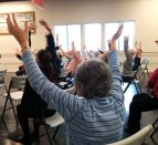 People sitting in chairs waving their arms in the air.