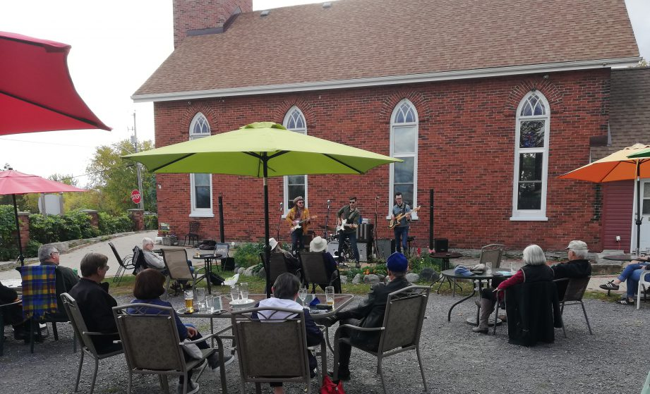 A patio with people sitting at tables watching live music, with a church in the background.