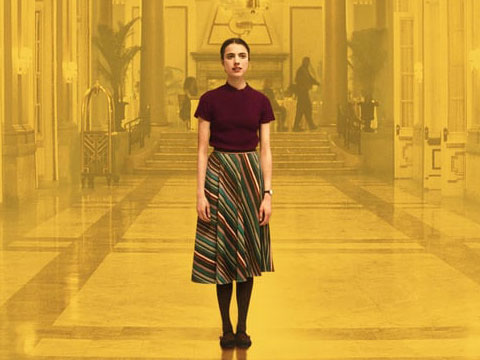 Hallway image with yellow filter on top. Woman standing in the centre of the image wearing a maroon top and patterned skirt.