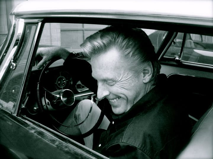 A black-and-white photo of a person sitting in a car.