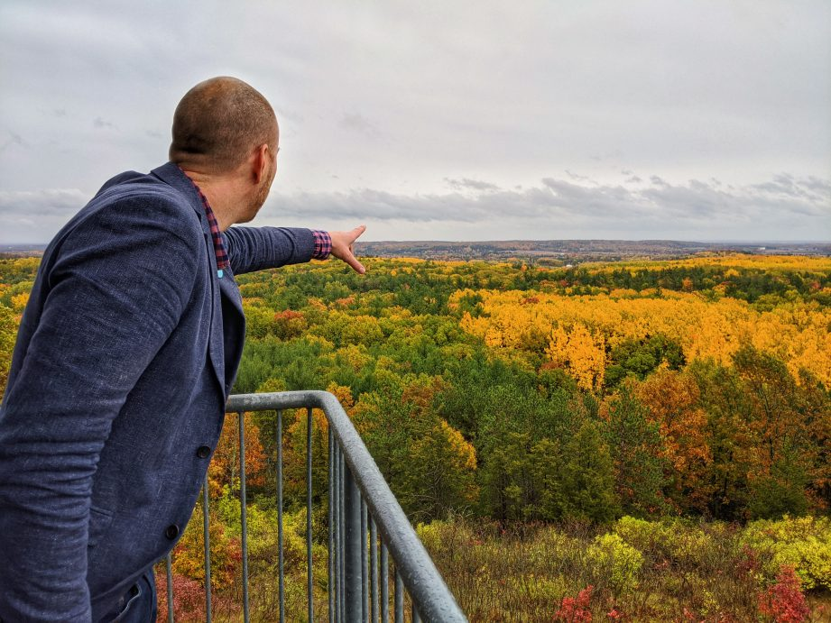 A person pointing out towards a landscape of colourful autumn trees.