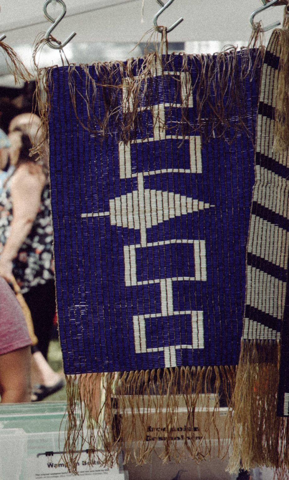 A row of beaded purple and white belts hanging from a wooden rod.